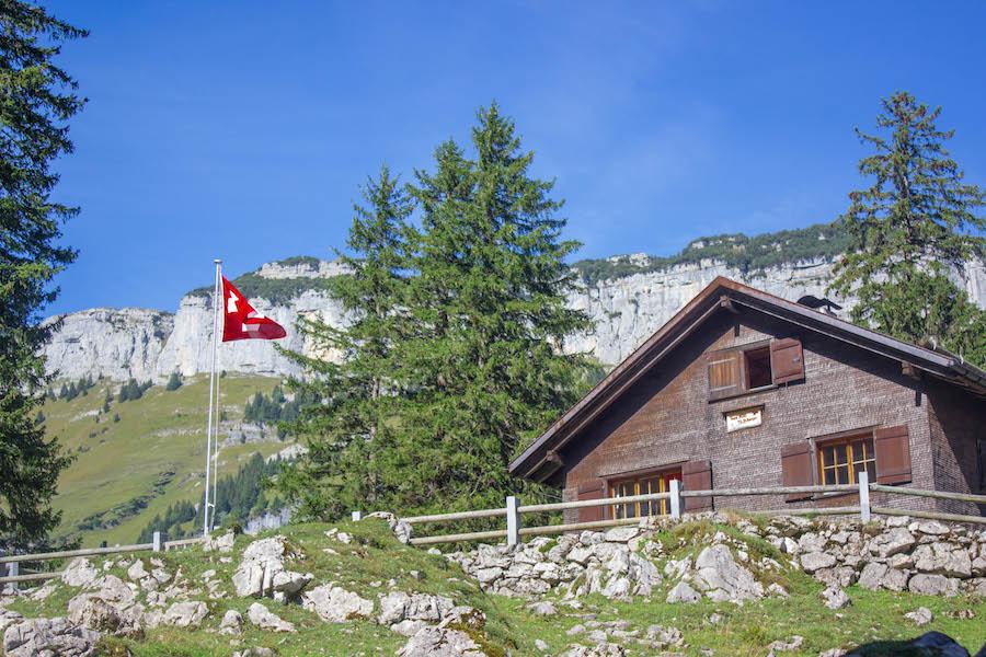 Wandern in den Schweizer Alpen - Berghütte mit schweizer Flagge